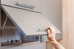 man hand open kitchen cupboard with handle, close up
