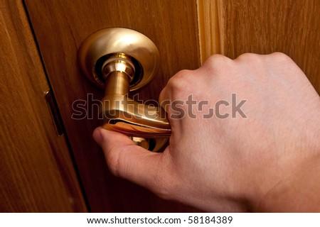 Man hand opening wooden door. Horizontal shot