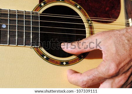 man hand play an acoustic twelve strings guitar - stock photo