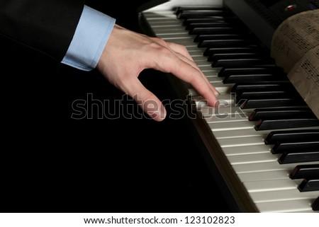man hand playing piano