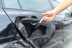 Man hand pointing on car bumper dented broken on black car door. injury car claim for insurance. Vehicle car crash damage accident on road. Insurance claim concept.