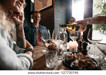 Man hand pouring white wine from the bottle into glasses with friends sitting around the table. Group of young people having food and drinks at restaurant. #527730748