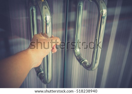 Man hand prepare to open the door to entering an Office background