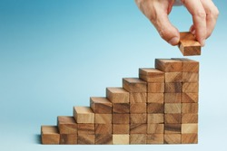 man hand put wooden blocks arranging stacking for development as step stair, on blue background. Concept of growth and success plan.