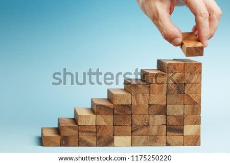 man hand put wooden blocks arranging stacking for development as step stair, on blue background. Concept of growth and success plan. #1175250220