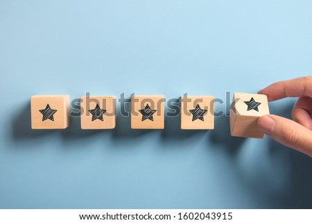 Man Hand putting wooden five star shape on blue background. Best Excellent Services Rating customer experience concept, Satisfaction.