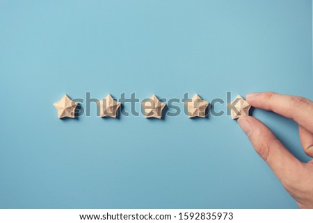 Man Hand putting wooden five star shape on blue background. Best Excellent Services Rating for Satisfaction.