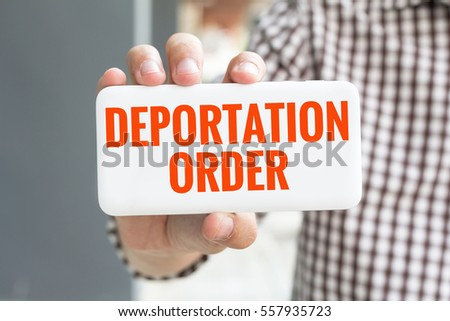 Shutterstock Man hand showing DEPORTATION ORDER word phone with  blur business man wearing plaid shirt.