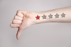 Man hand showing thumbs down and one star rating on the arm skin. Dislike