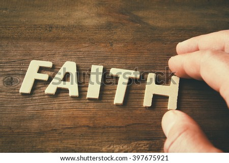 man hand spelling the word FAITH from wooden letters, retro style image  #397675921
