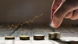 Man hand stacked coins with money saving concept and profit graph business finance.
