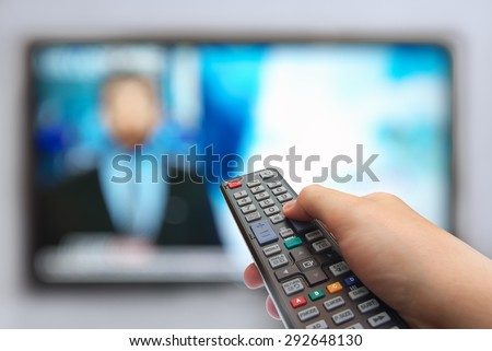 Man hand switches TV channels. Remote control in hand and TV