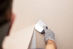 Man hand tear off old light wallpaper from wall.Preparing for home repair work.removing Wallpaper with a spatula, the process of updating the wall room repair. copy space