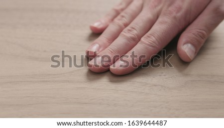 man hand touches black walnut board