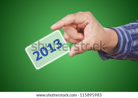 man hand touching button 2013 keyword, on green background