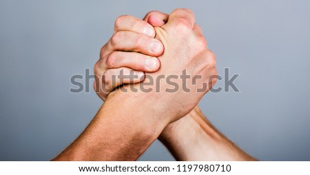 Man hand. Two men arm wrestling. Arms wrestling. Closep up. Friendly handshake, friends greeting, teamwork, friendship. Hand, rivalry, vs, challenge, strength comparison.