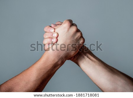 Man hand. Two men arm wrestling. Arms wrestling. Closep up. Friendly handshake, friends greeting, teamwork, friendship. Handshake, arms, friendship. Hand rivalry vs challenge strength comparison Photo stock ©