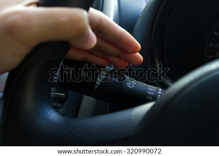 man hand use the signal switch. Car interior detail.