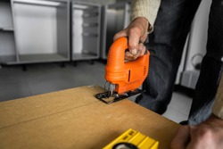 Man hand using electric jigsaw for cutting a fiberboard on a back side of a custom kitchen cabinet. Kitchen installation. Carpenter with a professional hand electric jigsaw instrument.
