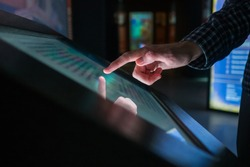 Man hand using interactive touchscreen display of electronic multimedia terminal at modern museum or exhibition. Evening time, low light illumination. Education, futuristic and technology concept