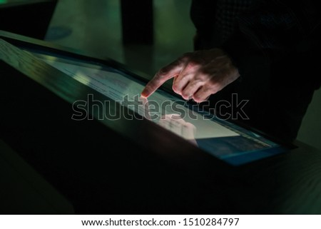 Man hand using interactive touchscreen display of electronic multimedia terminal at modern museum or exhibition. Evening time, low light illumination. Education, futuristic and technology concept #1510284797