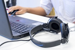 Man hand using keyboard and mouse to control laptop with headphone beside, working in music editing studio production