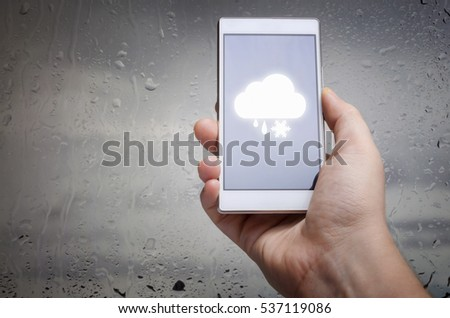 Man hand using mobile smart phone with glass window full of water droplets of raining day view with weather forecast widget mobile application program template