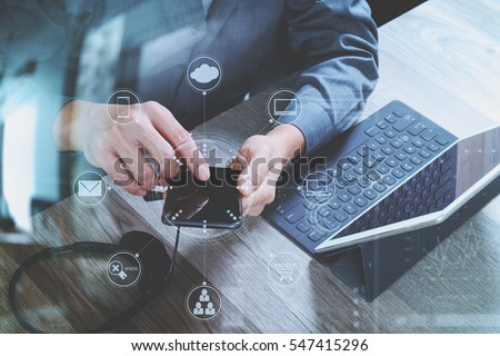 man hand using VOIP headset with digital tablet computer docking keyboard,smart phone,concept communication, it support, call center and customer service help desk,virtual interface icons screen