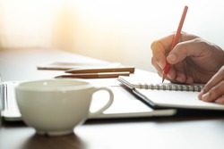 man hand using writing pencil memo on notebook paper or letter, diary on table desk office. Workplace for student, writer with copy space. business working and learning education concept.