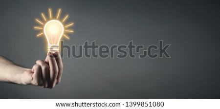 Man hand with a light bulb. Idea