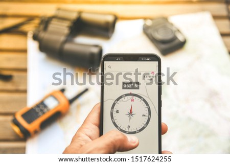 Man hand with electronic compass on smartphone, adventurous objects in background. Walkie talkie, binoculars and camera over a map ready for planning a travel route. Travelling, tech adventure concept