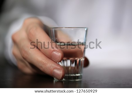 Man hand with glass of vodka , close up