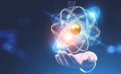 Man hand with hovering glowing gold and blue atom model over blurred dark blue background. Concept of science, chemistry and physics. Copy space toned image double exposure