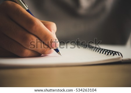man hand with pen writing on...