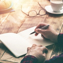Man hand with pen writing on notebook on a wooden table. Man working at coffee shop