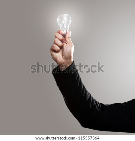 Man hand with shining lightbulb over gray background