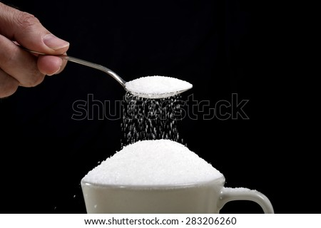 man hand with spoon pouring a crazy lot of it spilling out everywhere in full coffee cup in insane sugar addiction and unhealthy nutrition concept isolated on black background