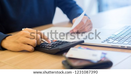 man hand write on notebook and calculate on calculator about debt bills pay monthly at the table in office and manage expense payroll for money risk and crisis financial and work from home concept Foto stock ©