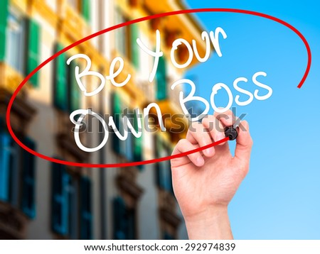 Man Hand writing Be Your Own Boss with black marker on visual screen. Isolated on city. Business, technology, internet concept. Stock Image