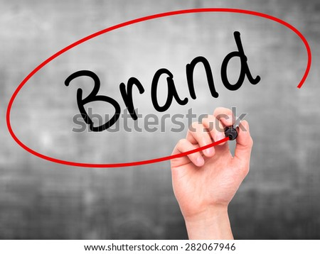 Man hand writing Brand on visual screen. Business,help, internet, technology concept. Isolated on grey. Stock Photo