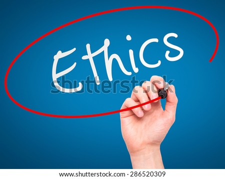 Man hand writing Ethics on visual screen. Business,help, internet, technology concept. Isolated on blue. Stock Photo