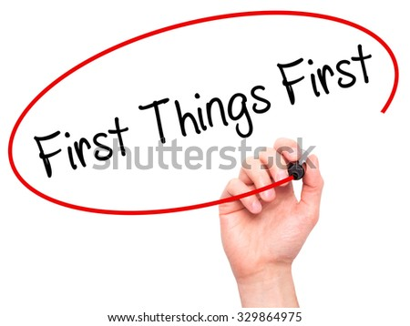 Man Hand writing First Things First with black marker on visual screen. Isolated on white. Business, technology, internet concept. Stock Photo #329864975