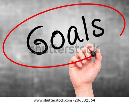 Man hand writing Goals on visual screen. Business,help, internet, technology concept. Isolated on grey. Stock Photo