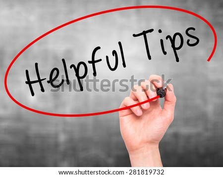 Man hand writing Helpful Tips on visual screen. Business,help, internet, technology concept. Isolated on grey. Stock Photo