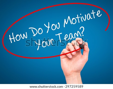 Man Hand writing How Do You Motivate Your Team? with black marker on visual screen. Isolated on blue. Business, technology, internet concept. Stock Photo