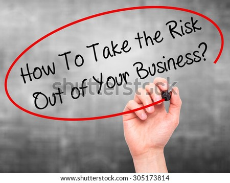 Man Hand writing How To Take the Risk Out of Your Business? with black marker on visual screen. Isolated on grey. Business, technology, internet concept. Stock Photo