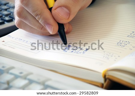 man hand writing in notebook numbers closeup