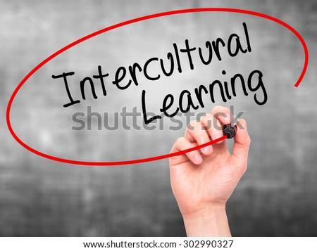 Man Hand writing Intercultural Learning with black marker on visual screen. Isolated on grey. Business, technology, internet concept. Stock Photo