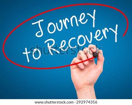 Man Hand writing Journey to Recovery with black marker on visual screen. Isolated on blue. Life, technology, internet concept. Stock Image