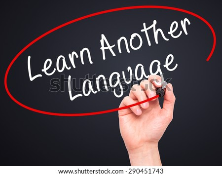 Man Hand writing Learn Another Language with black marker on visual screen. Isolated on black. Learn, technology, internet concept. Stock Image